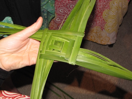Using reeds to weave a St Brigid's cross