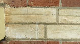 Hexafoil in brick near a window.