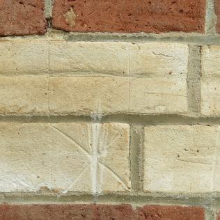Hexafoil in brick near a window.